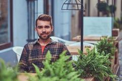 Портрет модного бородатого мужчины с стильной стрижкой, одетый в рубашке фланели, сидя в кафе outdoors стоковые изображения rf