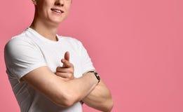 Портрет модного, брюнет, милый, положительный парень в белой футболке указывая его указательные пальцы на вас стоковые изображения