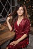 Портрет моды женщины в красном платье представляя на камере на предпо стоковая фотография