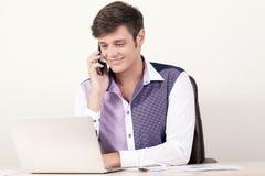 Портрет молодого бизнесмена используя мобильный телефон и компьтер-книжку пока сидящ на офисе и работающ в финансовом отчете Стоковое Изображение RF