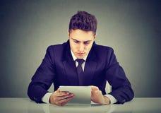 Портрет молодого бизнесмена используя ПК таблетки сидя на таблице Стоковые Фотографии RF