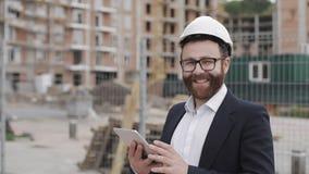 Портрет молодого бизнесмена с планшетом на смотреть строительной площадки усмехаясь к камере нося шлем безопасности и акции видеоматериалы