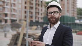 Портрет молодого бизнесмена с планшетом на строительной площадке смотря к камере нося шлем и костюм безопасности видеоматериал