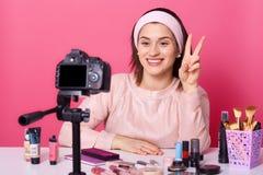Портрет молодого блоггера брюнета принимая видео через цифровую фотокамеру и показывая знак мира Жизнерадостная модель представля стоковые фото