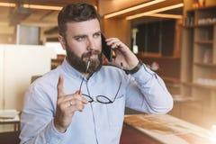 Портрет молодого бородатого бизнесмена в рубашке, держащ стекла в руке, поднимающ его указательный палец вверх, и говорящ на клет стоковые изображения