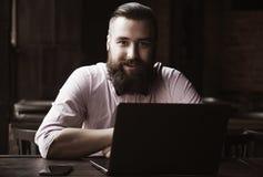 Портрет молодого бородатого бизнесмена работая с компьтер-книжкой Suc Стоковые Изображения RF