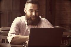 Портрет молодого бородатого бизнесмена работая с компьтер-книжкой Suc Стоковые Изображения