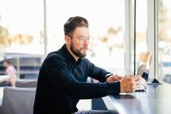 Портрет молодого бородатого телефона пользы бизнесмена на месте службы в современном офисе Стоковое Изображение