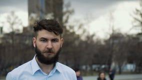 Портрет молодого взрослого человека с бородой и красивого класть на улицу 4k видеоматериал