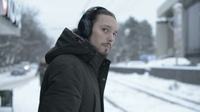 Портрет молодого длинн-с волосами человека с бородой в наушниках стоя на трамвайной остановке в зиме и ждать трамвай сток-видео