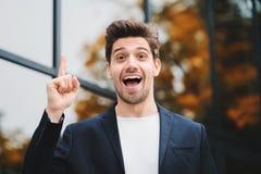 Портрет молодого думая обдумывая бизнесмена имея момент идеи указывая палец вверх на предпосылке офисного здания стоковое изображение
