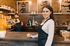 Портрет молодого женского владельца мелкого бизнеса - небольшой современной кофейни, уверенного положения женщины на счетчике с w стоковое фото