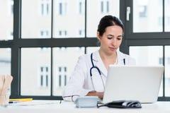 Портрет молодого женского врача работая на компьтер-книжке в офисе Стоковые Изображения