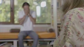 Портрет молодого женского psychotherapist рассматривая и поддерживая ее тревоженого и побеспокоенного мужского пациента в студии  акции видеоматериалы