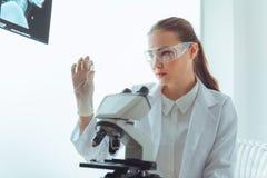 Портрет молодого исследования ученого используя микроскоп в работе стоковая фотография rf