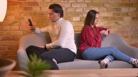 Портрет молодого кавказских человека и женщины сидя спина к спине на софе со смартфонами в домашней атмосфере видеоматериал