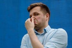 Портрет молодого кавказского человека закрывая его нос из-за ужасный пахнуть стоковая фотография rf