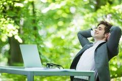 Портрет молодого красивого бизнесмена в костюме ослабляет на компьтер-книжке на руках таблицы офиса наверху в зеленом Forest Park Стоковые Изображения RF