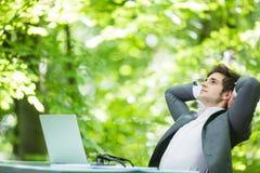 Портрет молодого красивого бизнесмена в костюме ослабляет на компьтер-книжке на руках таблицы офиса наверху в зеленом Forest Park Стоковая Фотография