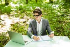 Портрет молодого красивого бизнесмена в костюме работая на компьтер-книжке на таблице офиса и беседа на телефоне с костюмом и дел Стоковая Фотография