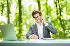Портрет молодого красивого бизнесмена работая на компьтер-книжке на таблице офиса и беседа на телефоне с костюмом и делают извеще Стоковая Фотография