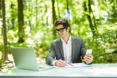 Портрет молодого красивого бизнесмена работая на компьтер-книжке на таблице офиса и беседа на телефоне с костюмом и делают извеще Стоковые Изображения