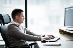 Портрет молодого красивого бизнесмена работая на компьютере Стоковые Изображения