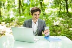 Портрет молодого красивого бизнесмена сидя на столе офиса в зеленых парке или лесе и работе на компьтер-книжке пока serfing в app Стоковые Изображения