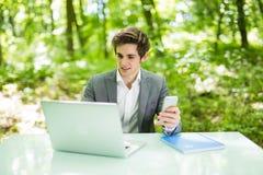 Портрет молодого красивого бизнесмена сидя на столе офиса в зеленых парке или лесе и работе на компьтер-книжке пока просматривающ Стоковые Фотографии RF