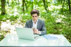 Портрет молодого красивого бизнесмена сидя на столе офиса в зеленых парке или лесе и работе на компьтер-книжке пока отправляющ СМ Стоковые Фото