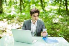 Портрет молодого красивого бизнесмена сидя на столе офиса в зеленых парке или лесе и работе на компьтер-книжке пока serfing в app Стоковые Фото