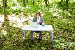 Портрет молодого красивого бизнесмена сидя на столе офиса в зеленых парке или лесе и работе на компьтер-книжке владение домашнего Стоковая Фотография RF