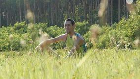 Портрет молодого красивого жизнерадостного человека сидя на траве в природе в лете на предпосылке леса и смотря вокруг видеоматериал