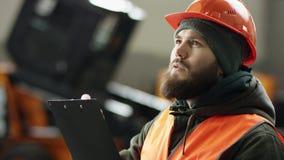 Портрет молодого красивого механика автомобиля в мастерской автомобиля, на заднем плане обслуживания Он приходит в гараж в a сток-видео