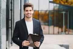 Портрет молодого красивого человека в куртке с документами, счетами за коммунальные услуги, отчетом Бизнесмен около офисного здан стоковое фото