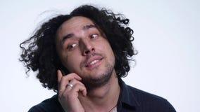 Портрет молодого красивого человека говорит на телефоне и смеяться над на белой предпосылке сток-видео