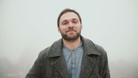 Портрет молодого красивого человека при борода стоя на фоне Эйфелевой башни и смотря камеру видеоматериал