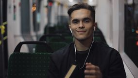 Портрет молодого красивого человека сидя на общественном транспорте Он смотрит камеру, носит шлемофон и закрыл книгу видеоматериал