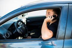 Портрет молодого красивого человека управляя автомобилем и говоря на мобильном телефоне стоковая фотография