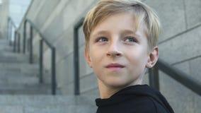 Портрет молодого мальчика смотря назад, счастливое детство, светлое будущее, замедленное движение сток-видео