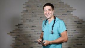 Портрет молодого мужского доктора в зеленой медицинской форме имея потеху Phonendoscope молодого специалиста нося на шеи 4K сток-видео