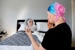 Портрет молодого онкологического больного в головном платке смотрит удивленным на отражении в зеркале стоковые фото