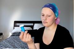 Портрет молодого онкологического больного в головном платке смотрит далеко от бутылки пилюлек она держит Стоковое Изображение