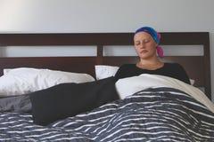 Портрет молодого онкологического больного в головном платке спать в кровати стоковая фотография rf