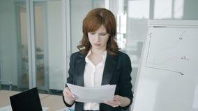 Портрет молодого отчета о чтения коммерсантки в офисе сток-видео