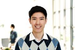 Портрет молодого привлекательного азиатского творческого человека усмехаясь и смотря камеру стоковое изображение rf