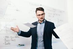 Портрет молодого привлекательного темн-с волосами парня в стеклах бросая документы в офисе Он стоит около белого стола с стоковые изображения