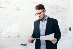 Портрет молодого привлекательного темн-с волосами парня в стеклах проверяя документы в офисе Он стоит около белого стола с стоковые фото