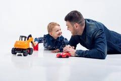 Портрет молодого привлекательного усмехаясь отца играя при освещенное его Стоковая Фотография