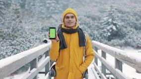 Портрет молодого привлекательного человека в одеждах зимы показывая смартфон с зеленым экраном смотря в камеру видеоматериал